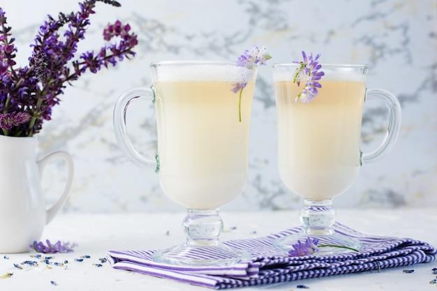 グラスにミルク、泡、ラベンダーを入れたラテと白いテーブルの水差しに花の花束。アロマコーヒー