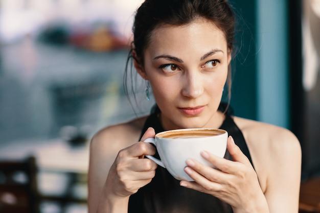 Уточненная женщина наслаждаясь капучино или latte на живой, красочной предпосылке внутри помещения.