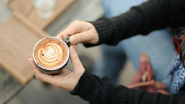 Текстура сердца кофе latte в руке туристов.