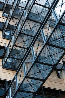 Lattice metal walkways between two modern buildings.