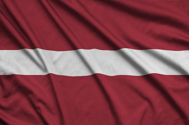 Latvia flag is depicted on a sports cloth fabric with many folds.