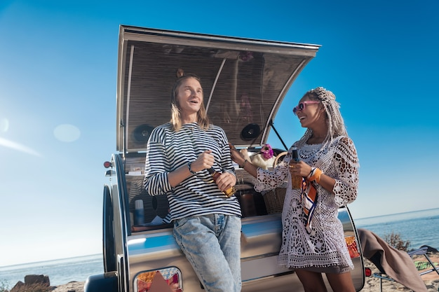 Laugh and beer. stylish modern couple feeling relaxed while laughing and drinking beer near their mobile home