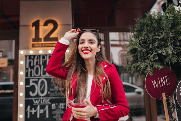 Ragazza adorabile di risata in giacca rossa che cammina per strada