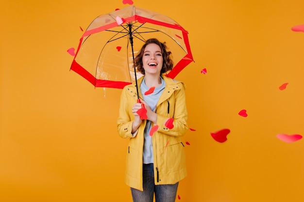 Смеющаяся очаровательная девушка с зонтиком, смотрящая на летающие сердца. крытый портрет элегантной кудрявой дамы носит желтый наряд, стоящий с зонтиком.