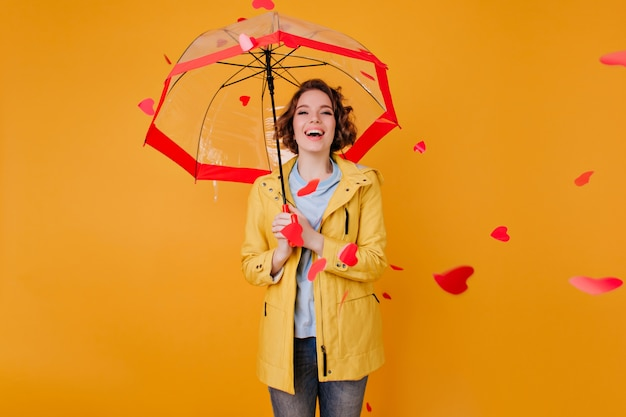 Laughing adorable girl with parasol looking at flying hearts. indoor portrait of elegant curly lady wears yellow attire standing with umbrella.