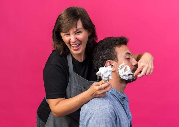 Смеющаяся взрослая кавказская женщина-парикмахер в униформе держит кисть для бритья с пеной и бородой молодого человека с опасной бритвой, изолированной на розовом фоне с копией пространства