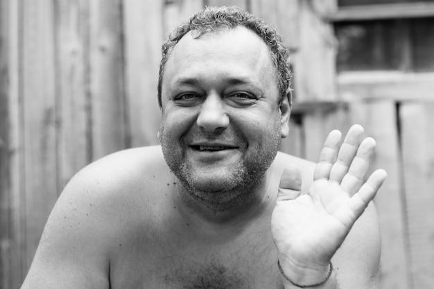 村の家の中庭で裸の胴体を持った大人の無精ひげを生やした男性のアルコール依存症を笑う。閉じる。黒と白の写真。