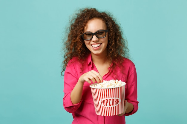 Laughing african girl in 3d imax glasses watching movie film and holding popcorn isolated on blue turquoise wall background in studio. people emotions in cinema, lifestyle concept. mock up copy space.