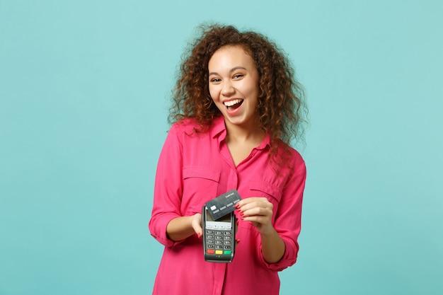 笑うアフリカの女の子は、処理するためにワイヤレスの近代的な銀行決済端末を保持し、青いターコイズブルーの背景に分離されたクレジットカード決済を取得します。人々の感情、ライフスタイルの概念。コピースペースをモックアップします。