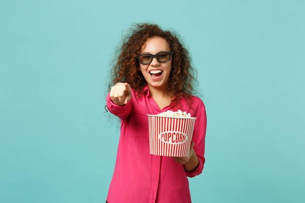 3d 아이맥스 안경을 쓰고 영화를 보고 있는 아프리카 소녀가 푸른 청록색 배경에 격리된 카메라에 검지 손가락을 가리키는 팝콘을 들고 웃고 있습니다. 영화 개념에서 사람들의 감정. 복사 공간을 비웃습니다.