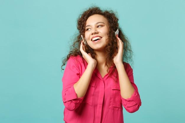 スタジオで青いターコイズブルーの背景に分離されたヘッドフォンで音楽を聴きながら、カジュアルな服を着てアフリカの女の子を笑っています。人々の誠実な感情、ライフスタイルのコンセプト。コピースペースをモックアップします。