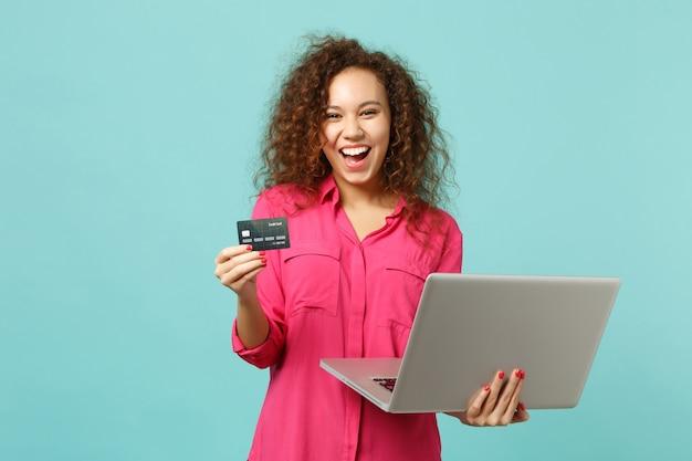 ラップトップpcコンピューターを使用してカジュアルな服装でアフリカの女の子を笑って、スタジオで青いターコイズブルーの背景に分離されたクレジット銀行カードを保持します。人々の誠実な感情のライフスタイルの概念。コピースペースをモックアップします。