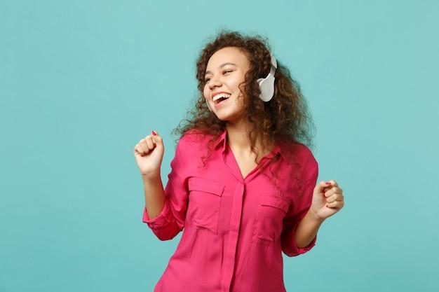 ヘッドフォンで音楽を聴き、青いターコイズブルーの壁の背景に分離されたダンスをピンクのカジュアルな服で笑うアフリカの女の子。人々の誠実な感情、ライフスタイルのコンセプト。コピースペースをモックアップします。