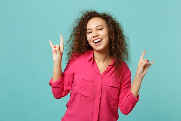 青いターコイズブルーの壁の背景に分離されたヘビーメタルロックサインを描いた角を示すピンクのカジュアルな服を着て笑うアフリカの女の子。人々の誠実な感情のライフスタイルの概念。コピースペースをモックアップします。