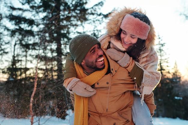 自然環境で冬の週末を楽しんで楽しんでいる間、彼の幸せなガールフレンドにピギーバックを与えるウィンターウェアでアフリカの男を笑う