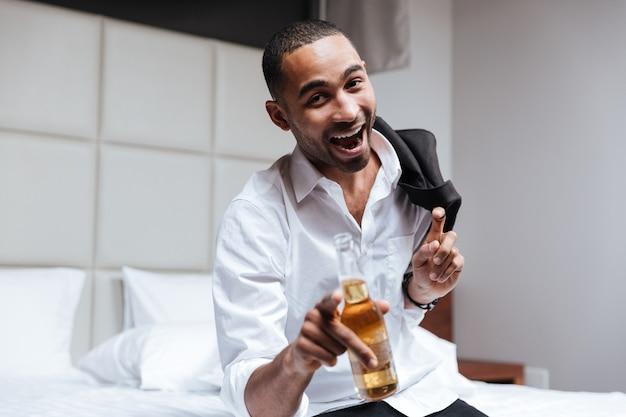 Смеющийся африканский мужчина в рубашке держит пиво и смотрит в камеру в гостиничном номере