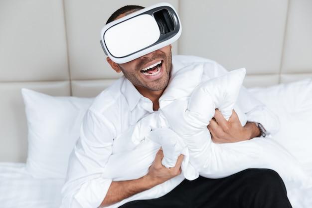 Смеющийся африканский мужчина в рубашке с помощью устройства виртуальной реальности на кровати в отеле