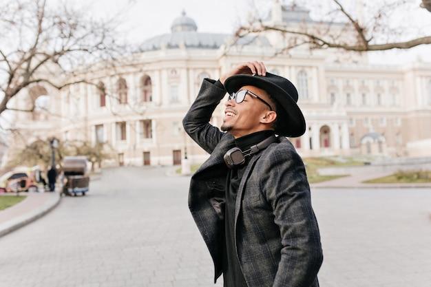 아름 다운 건물 거리에 서있는 유행 재킷에 아프리카 남자를 웃 고있다. 오래 된 도시에서 기쁨으로 포즈를 취하는 이어폰을 가진 mulatto 남자.