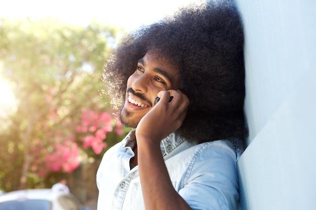 携帯電話で話す壁に傾いている笑っているアフロ男
