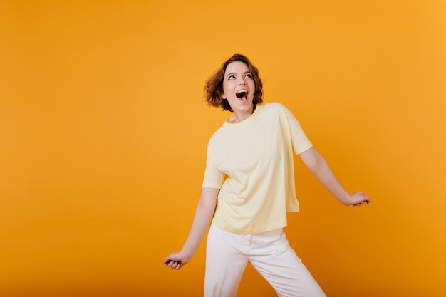 밝은 주황색 벽에 포즈를 취하는 문신과 놀라운 소녀를 웃고 있습니다. 트렌디 한 캐주얼 복장에 아름다운 유럽 아가씨.