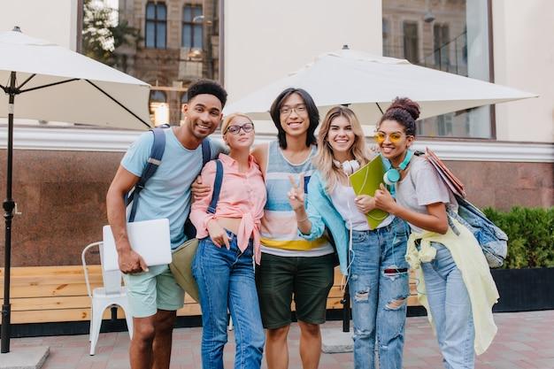 Смеющийся азиатский мальчик в очках и шортах обнимает очаровательных блондинок перед летним кафе. радостные студенты пришли в ресторан под открытым небом отметить окончание экзаменов