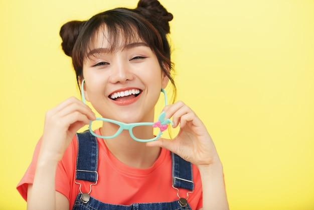 スタジオでポーズをとって、明るい色のフレームでメガネを保持しているアジアの女の子を笑ってください。