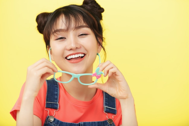 Laughing asian girl posing in studio and holding glasses in brightly colored frame