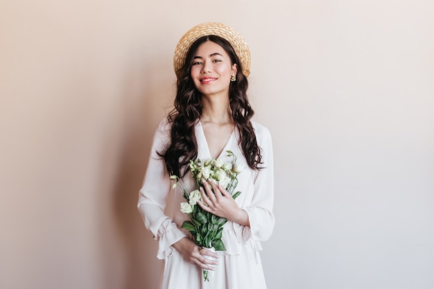 Laughing asian woman holding white flowers. front view of japanese woman in straw hat posing with bouquet.