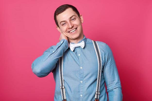 白いボタンと青いシャツを着て、首に片手を入れて、右側に頭を傾けて、魅力的な男の子を笑ってください。