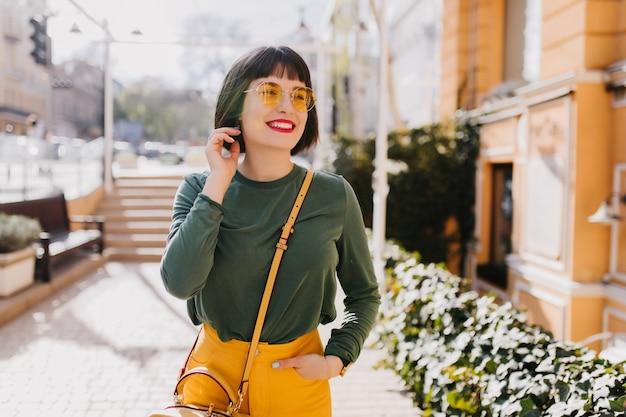 トレンディな春の服装で魅力的な女の子を笑って屋外で冷やします。幸せな白人女性の写真はサングラスと黄色のハンドバッグを身に着けています。