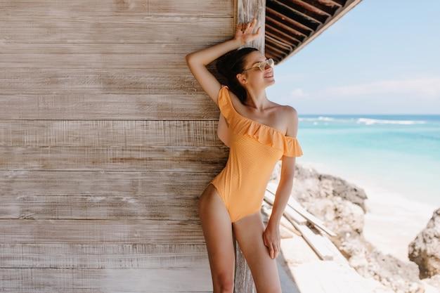 Смеющаяся привлекательная девушка позирует с удовольствием в летние выходные. утонченная молодая женщина в оранжевых купальниках, стоящая возле дома на берегу моря.