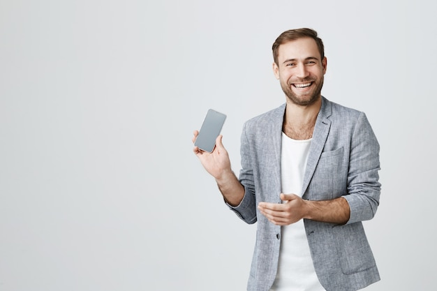 Laughing attractive man showing smartphone screen