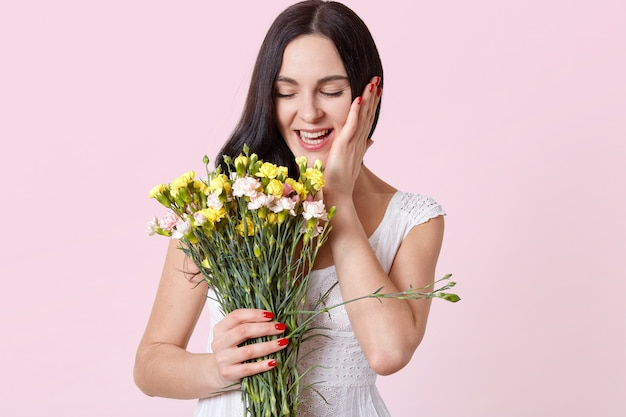 Laughing attractive young brunette model with closed eyes holding beautiful flowers in one hand, touching her face with other one