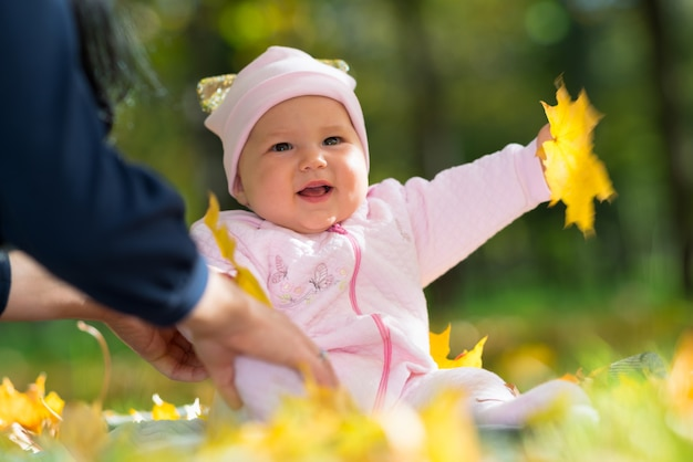Laughing baby girl playing with autumn leaves with her mother outdoors in the park in a low angle portrait