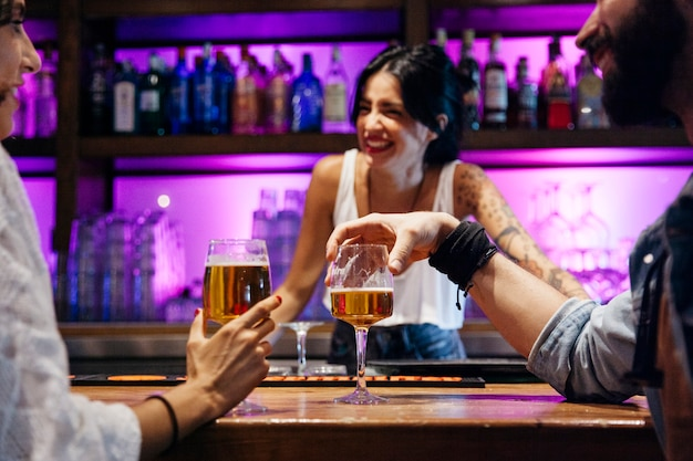 Laughing bartender and two clients