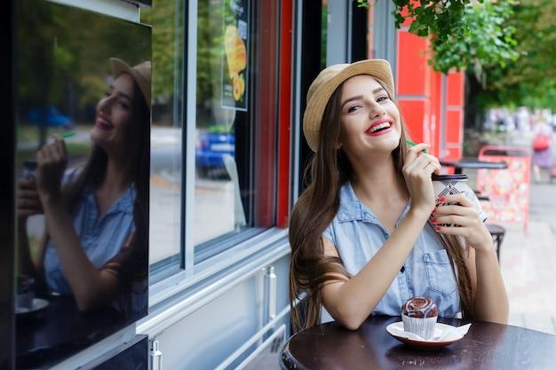 マフィンとコーヒーを飲む屋外カフェで美しい少女を笑う