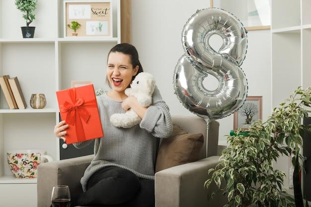 Смеющаяся красивая девушка в день счастливой женщины держит подарок с плюшевым мишкой, сидящим на кресле в гостиной