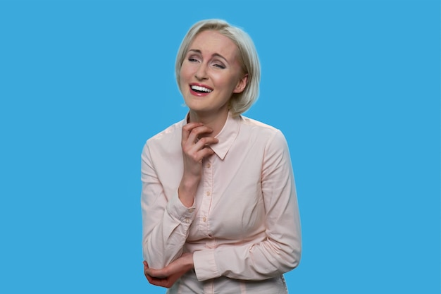 Laughing beautiful lady in white blouse. cheerful formal-dressed woman isolated on blue background.