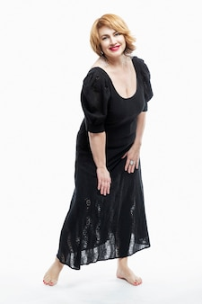 검은 드레스에 빨간 머리를 가진 아름다운 중년 여성을 웃고 맨발로 전체 성장에 선다.