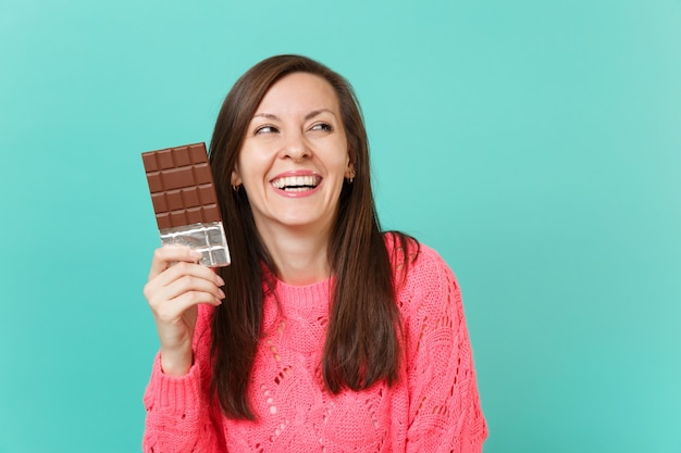 Laughing beautiful young girl in knitted pink sweater looking aside hold in hand chocolate bar isolated on blue turquoise wall background studio portrait. people lifestyle concept. mock up copy space.