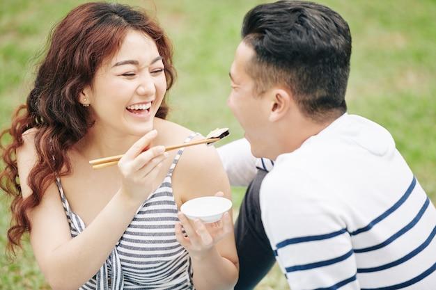 彼らが公園でロマンチックなピクニックを楽しんでいるときに彼氏にスチの作品を与える美しい若いベトナム人女性を笑う