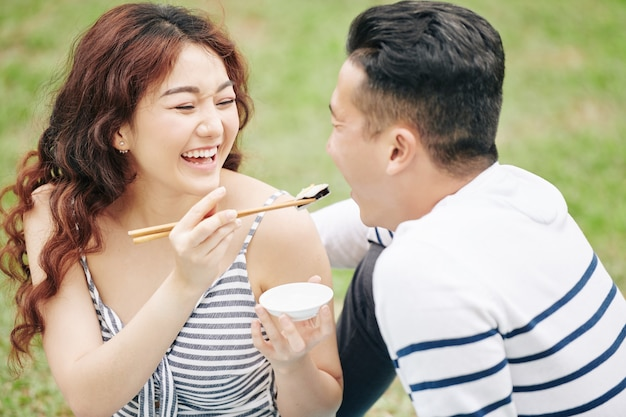 Laughing beautiful young vietnamese woman giving piece of suchi to boyfriend when they are enjoying romantic picnic in park