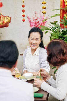 Laughing beautiful young woman celebrating chinese new year with family