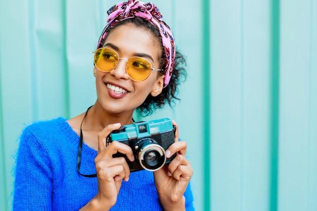 レトロなカメラを押しながらカメラ目線のかわいい髪型と黒の女の子を笑っています。
