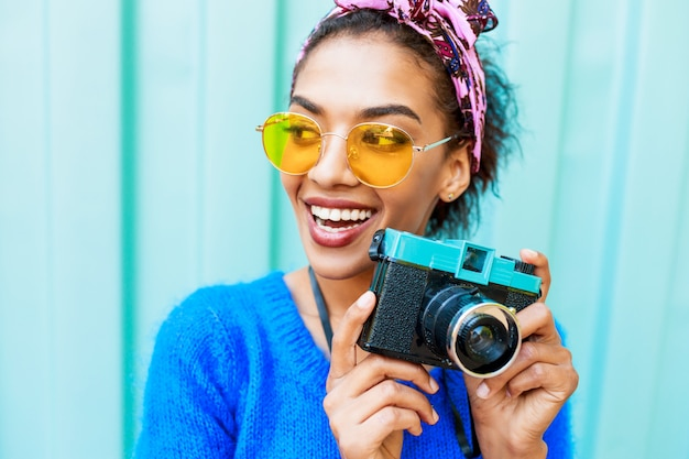 Laughing black girl with cute hairstyle holding retro camera and looking at camera.