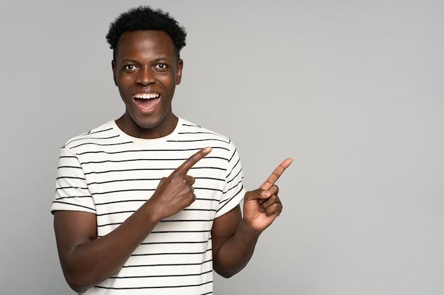 Смеющийся темнокожий мужчина показывает пальцами в сторону, смотрит в камеру, показывая пустое место для рекламы