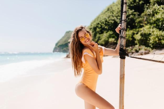 リゾートで設定されたバレーボールの近くで踊るサングラスで笑う至福の少女。エキゾチックなビーチで浮気する水着姿の格好良い白人女性モデル。