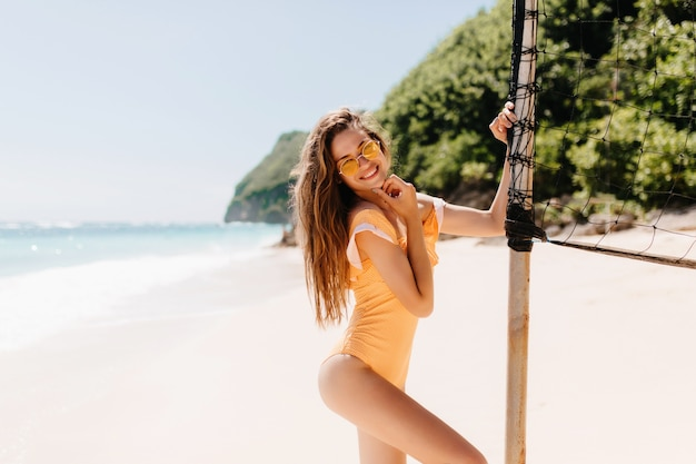 Laughing blissful girl in sunglasses dancing near volleyball set at resort. good-looking caucasian female model in swimsuit fooling around at exotic beach.