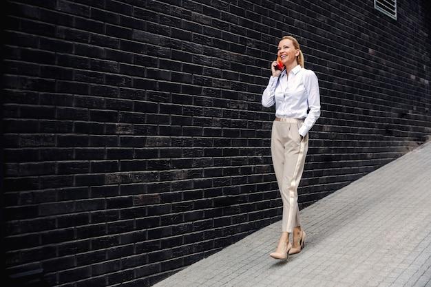 Смеющаяся блондинка модная бизнесвумен гуляет по улице и разговаривает по телефону