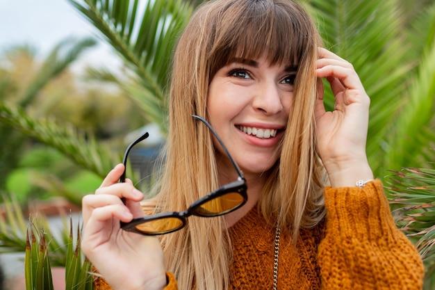 Смеющаяся блондинка в стильных солнцезащитных очках позирует на набережной в барселоне
